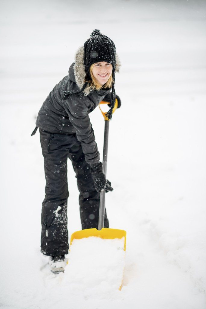 Shovelling snow off her driveway after a storm