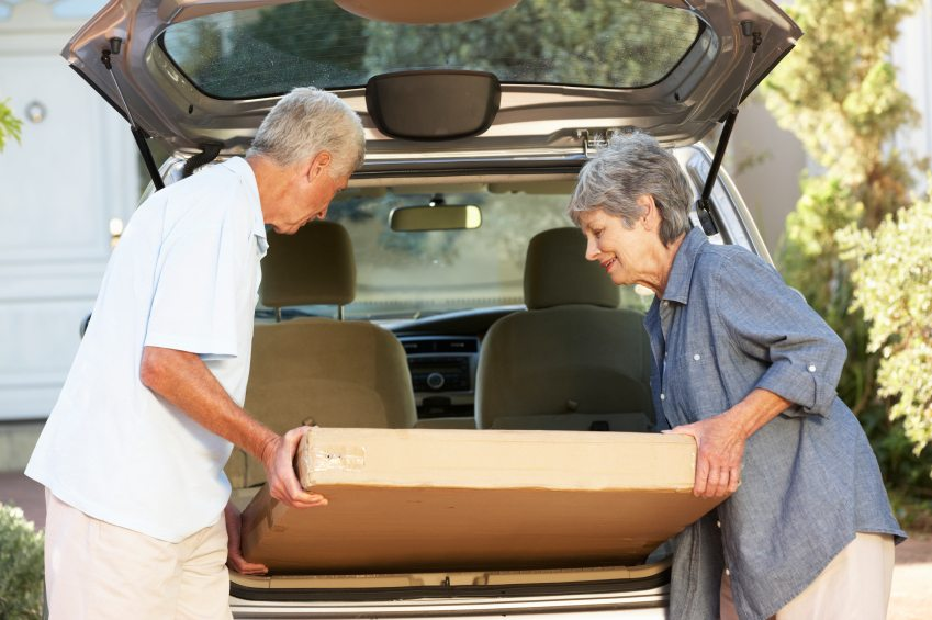Senior Couple Loading Large Package Into Back Of Car