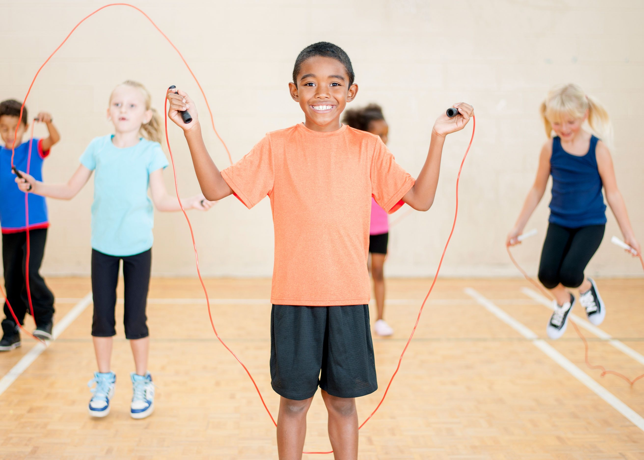 Happy child skipping rope in gym class