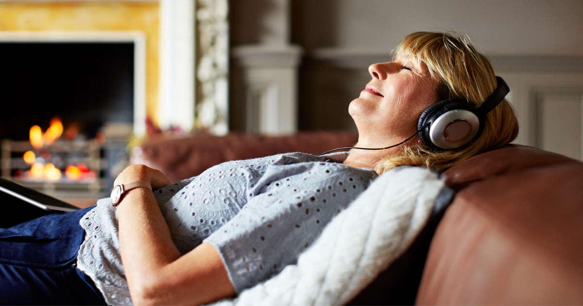 Woman happily reclining back with headphones over her ears