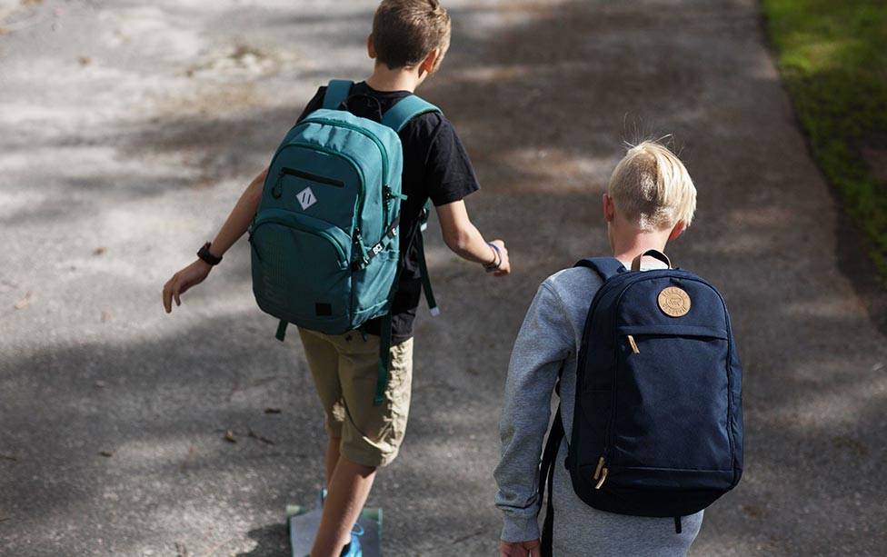 Young boys walking to school with backpacks on