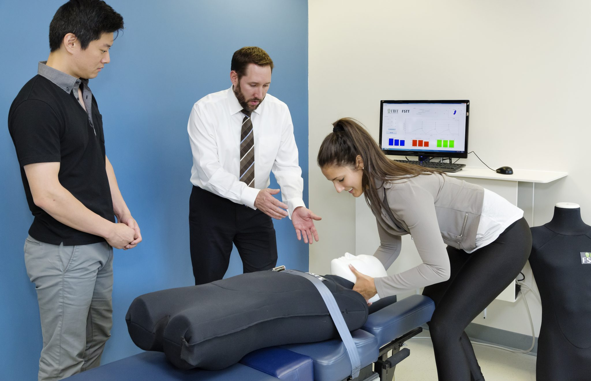 Female chiropractic student practicing adjustment technique in simulation lab